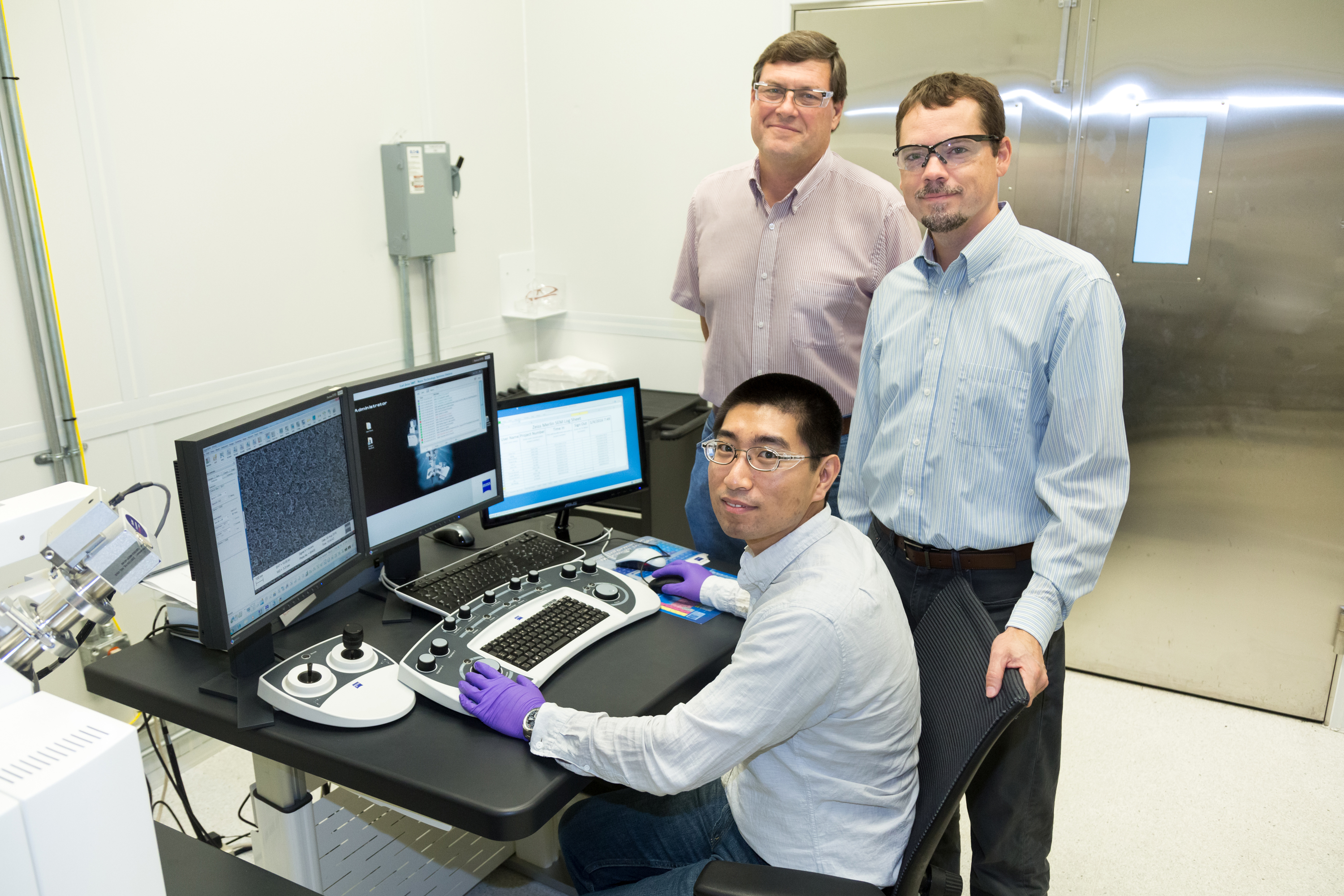 Oak Ridge National Laboratory's Yang Song (person seated), Dale Hensley (person standing left) and Adam Rondinone examine a carbon nanospike sample with a scanning electron microscope.