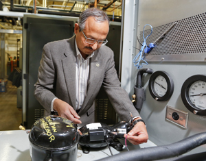 ORNL's Pradeep Bansal examines an Embraco linear compressor, which will be used in a Whirlpool-ORNL project aimed at building a more energy-efficient refrigerator.