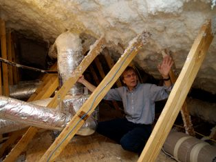 ORNL's Jeff Christian points out the insulating foam used to seal the attic in a deep retrofit house.
