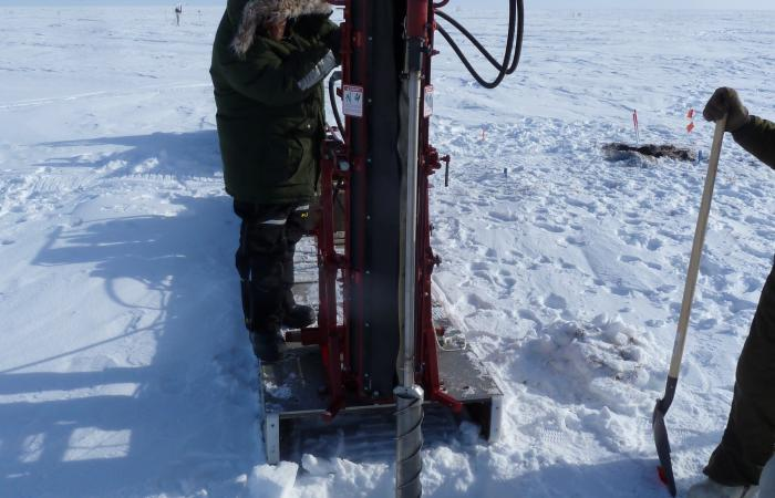 ORNL's Kenneth Lowe operates a hydraulic drill to collect frozen soil cores from Barrow for incubation experiments.