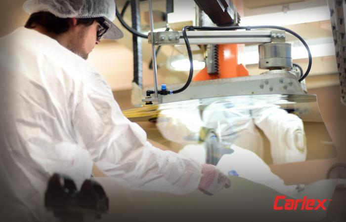 Inside the clean room, Carlex employees carefully place a PVC interlayer between two pieces of windshield glass. Credit: Carlex Glass America, LLC