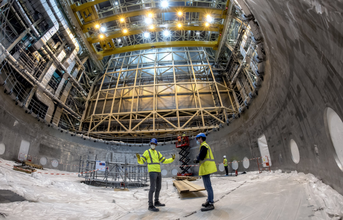 "ITER staff inside the ""dish"" of the cryostat base. The 1250 ton base will initially be lifted just a few centimeters in preparation for its transfer to the tokamak pit. Photo: ITER Organization"
