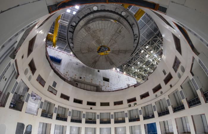 The 1250 ton cyrostat base is positioned over the ITER tokamak pit for installation. This base is the heaviest lift of tokamak assembly. Credit: ITER Organization