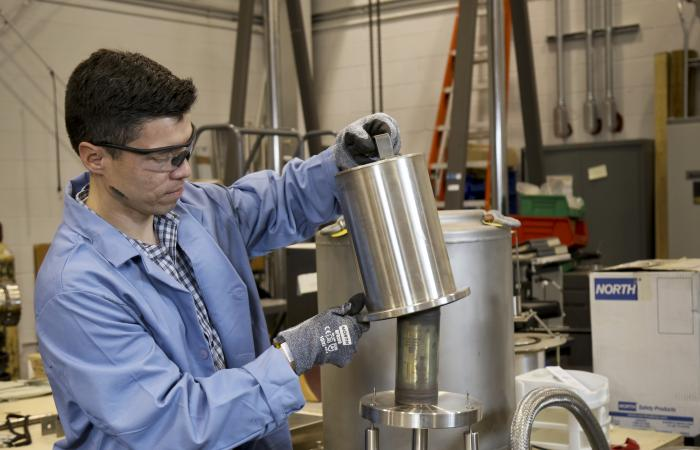 Oscar Martinez loads a special form capsule into the leak tester for a helium leak test in the packaging facility of the National Transportation Research Center. Credit: Jason Richards/ORNL, U.S. Dept. of Energy