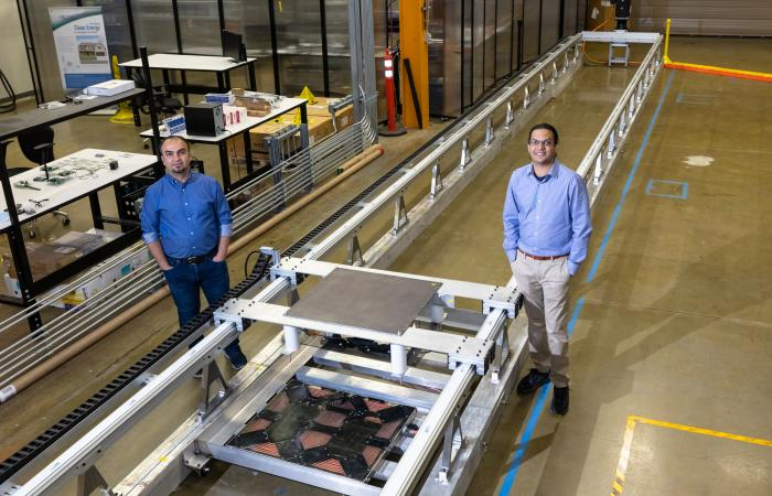 L-R: ORNL's Omer Onar and Veda Galigekere with the dynamic wireless charging test bed at ORNL's Grid Research Integration and Deployment Center. Credit: Carlos Jones, ORNL/U.S. Dept. of Energy