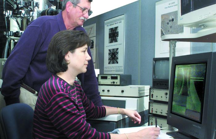 During DOE programs to advance industrial ceramic matrix composites, ORNL's Karren More (foreground, with Larry Walker) used transmission electron microscopy and other techniques.