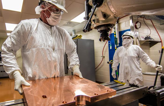Working in a cleanroom nearly a mile underground, Randy Hughes (foreground) is the primary on-site machinist for the MAJORANA DEMONSTRATOR experiment. The innermost shield and detector components are fabricated from ultrapure copper produced by electrofor
