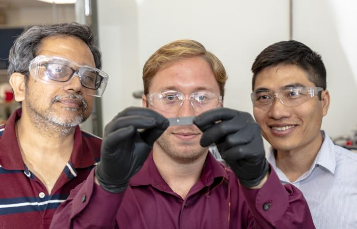 From left, Naskar, Bowland and Nguyen examined a cantilever made of fiber-reinforced composite with the fibers aligned in one direction and measured its electrical resistance in response to stress. Credit: Carlos Jones/Oak Ridge National Laboratory, U.S.