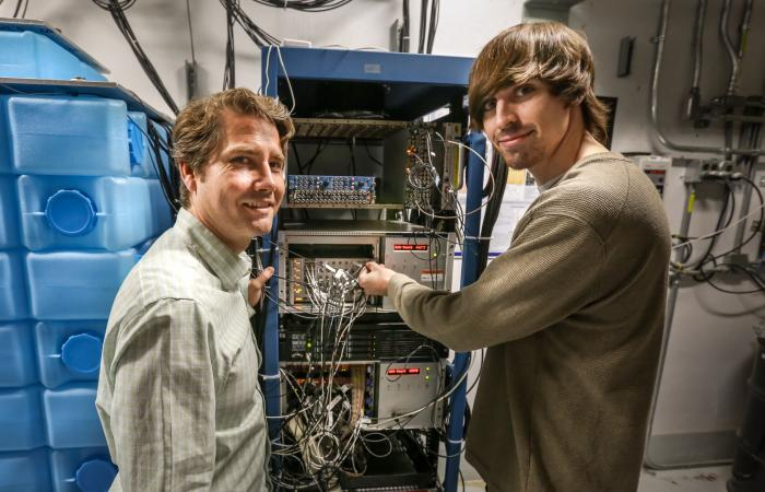 From left, Jason Newby of ORNL and Brandon Becker of the University of Tennessee–Knoxville examine equipment that will collect data for COHERENT. Becker, a graduate student, will model, simulate and analyze interesting physics that result from interaction