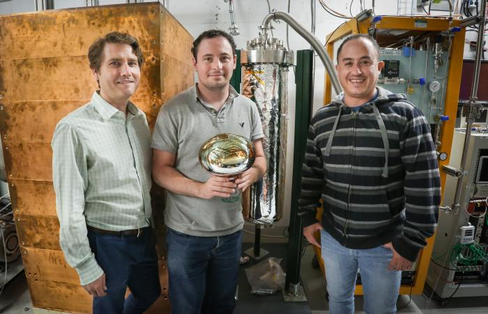 From left, Jason Newby of ORNL, Jacob Zettlemoyer of Indiana University and Hector Moreno of New Mexico State University work on the COHERENT experiment to detect neutrinos at the SNS. Shown is an 8-inch wide photomultiplier for a liquid-argon detector wi