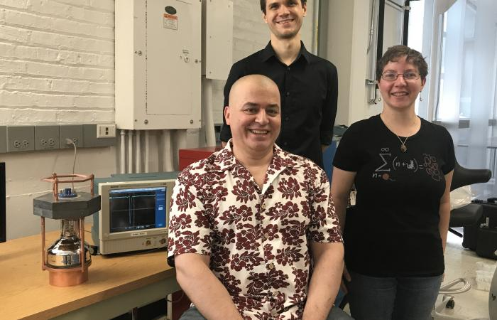 From left, Professor Juan Collar with Bjorn Scholz and Nicole Fields led detector development at the University of Chicago. A four-pound prototype detector, a replica of the 32-pound (14.5 kilogram) one used at the SNS, is at left. Fields's 2015 Ph.D. the