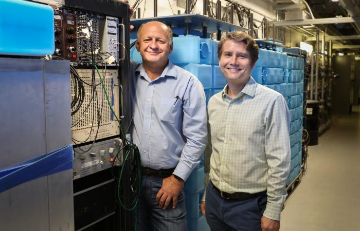 From left, Jason Newby of ORNL and Yuri Efremenko of the University of Tennessee–Knoxville/ORNL check equipment for the COHERENT experiment at the SNS. In 2005 Efremenko and others proposed a neutrino facility at the SNS; that vision is realized in the cu