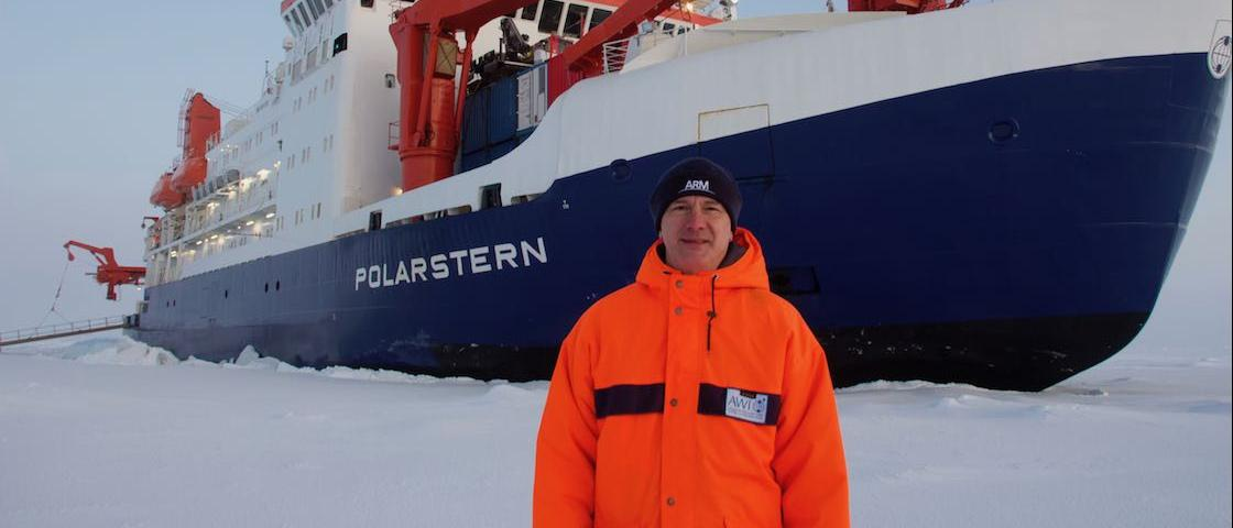 Misha Krassovski, a computer scientist at Oak Ridge National Laboratory, stands in front of the Polarstern, a 400-foot long German icebreaker. Krassovski lived aboard the Polarstern during the first leg of the MOSAiC mission, the largest polar expedition ever. Credit: Misha Krassovski/Oak Ridge National Laboratory, U.S. Dept. of Energy