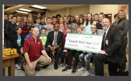 ORNL Director Thomas Zacharia (center, seated) visited Robertsville Middle School to present a check in support of the school's CubeSat efforts.