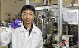 Zhenglong Li, an ORNL scientist in the Energy and Transportation Science Division, holds a sample of a catalyst material used to covert ethanol into butene-rich mixed olefins, important intermediates that can then be readily processed into aviation fuels. Credit: Carlos Jones/ORNL, U.S. Dept. of Energy