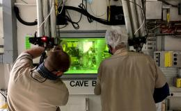 Technicians John Dyer and T. Dyer use a manipulator arm in a shielded cave in ORNL's Radiochemical Engineering Development Center to separate concentrated Pm-147 from byproducts generated through the production of Pu-238.