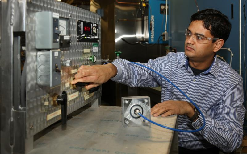 ORNL researcher Kaushik Biswas demonstrates how a self-healing barrier in a vacuum insulation panel can recover from a puncture.