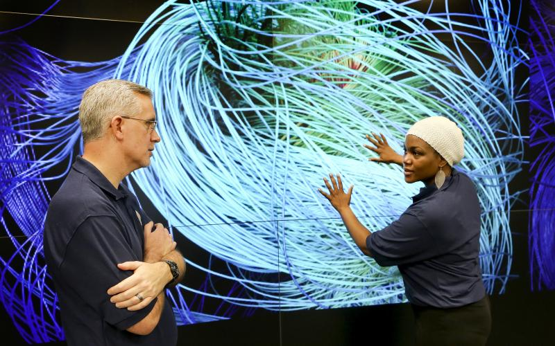 Scientists discuss a simulation in the EVEREST visualization theater of the Oak Ridge Leadership Computing Facility.