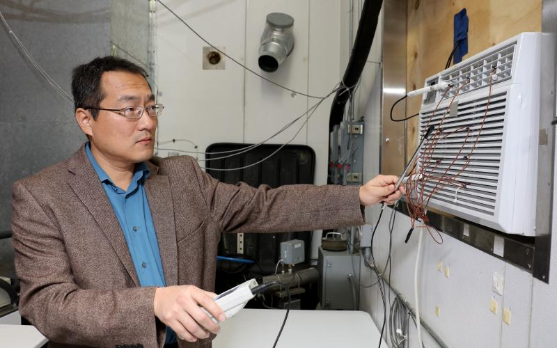 Oak Ridge National Laboratory's Bo Shen works with a prototype window air conditioning unit that cools using propane, which lowers costs, increases efficiency and benefits the environment.