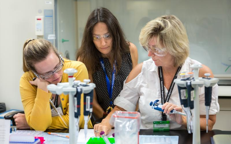 Flora Meilleur (middle) works with teachers participating in her project, helping them mix the protein solution lysozyme with a salt solution to form a crystal. The teachers mix the solutions in various concentrations and ratios and observe the results.