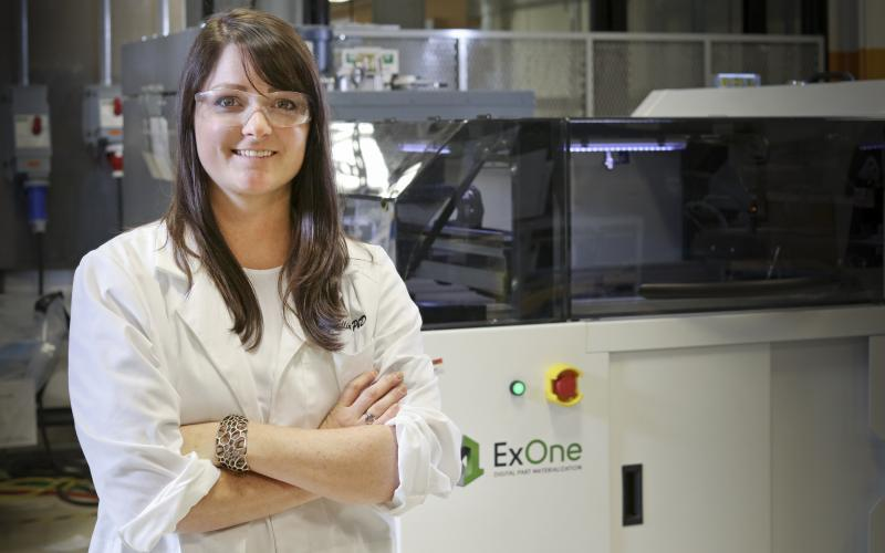 Researcher Amy Elliott and the ExOne binder jet printer at the Manufacturing Demonstration Facility.